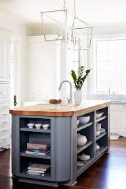 gorgeous white and gray kitchen features a darlana linear chandelier hung over a stained wood countertop accenting a curved gray island finished with