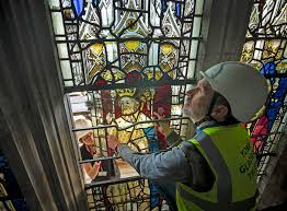 nick and conservator zoe harrigan remove a stained glass windows panel