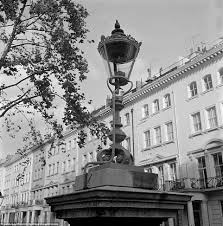 past a gas street lamp is seen outside the grand terraced houses of ennismore gardens