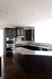 This fantastic kitchen has a sleek dark wooden floor. The cabinets in this  space correspond