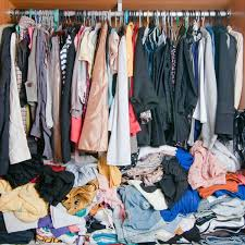pile of messy clothes in closet untidy cluttered woman wardrobe shutterstock id 601072265