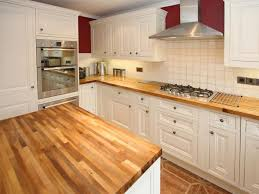 white island and cabinets small simple elegant kitchen light wooden countertop double wall ovens backsplash tile metallic vent hood