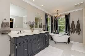 traditional master bathroom with freestanding clawfoot tub and square field tile