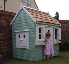 childs playhouse with wooden cedar shingles opening windows and window boxes