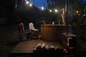 relaxing lighting. Friends Relaxing, Soaking In Hot Tub Under String Lights On Night Patio Relaxing Lighting G
