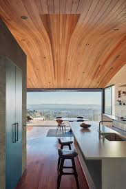 This modern home has a curved wood ceiling, The long sections of wood help  to