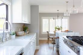 white kitchen boasts white and gray quartz countertops with taupe geometric backsplash tiles and stainless steel appliances
