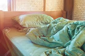 unmade bed side view. Green Pillow And Blanket With Wrinkle Messy On Bed In Vintage Wooden Bedroom Lighting Upper Unmade Side View C