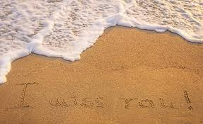 dramatic inscription miss you on wet golden beach sand