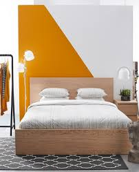 A Simple Clean Bedroom With A Graphic Orange And White Wall Custom How To Clean Bedroom Walls