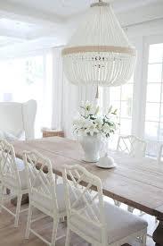 white orbit chandelier dining table is a restoration hardware salvaged wood trestle table in natural lighting is sham orbit white milk beads white orbit