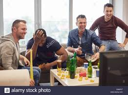 group of men watching sports event on television snacks and group of men watching sports event on television snacks and beers smiling