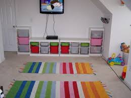 furniture white wooden shelves with colorful plastic basket inside plus colorful striped rug on grey