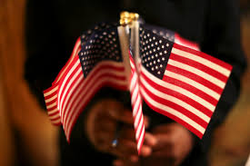 majority of americans favor path to citizenship newshour a w holds a cluster of u s flags during a u s citizenship and immigration services naturalization