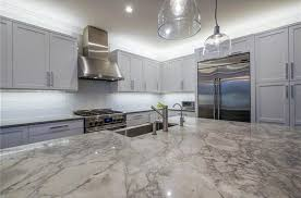 luxury kitchen with calacatta carrara marble counter gray cabinets and white backsplash