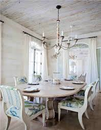 rustic dining room with white tone andfl pattern cushioned chair and oval table and vintage chandelier