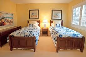 A Small Bedroom With Two Single Beds And Filled With Yellow Accent. The  Wood Of