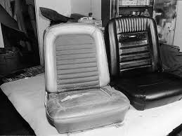 one of our completed black deluxe interior front seats sits next to the original blue standard interior bucket seat for comparison