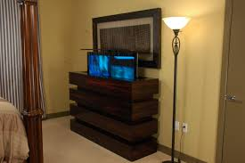 Here Is A TV Lift Cabinet Showing TV Half Way Up Against A Wall In - Bedroom tv lift cabinet
