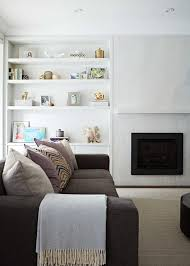 welcoming living room features styled white built in shelves fixed above white cabinets and beside a