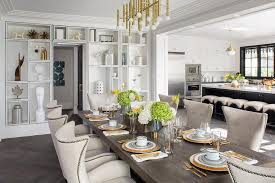 jonathan adler meurice rectangular chandelier lights a walnut stained rectangular dining table surrounded by cream upholstered wingback chairs placed on a