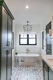 the freestanding tub sits beneath the stunning arnold chandelier also from gabby home a white subway tile wainscot with black grout protects walls for