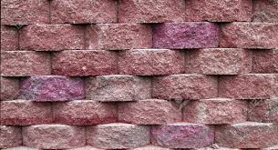blocks on a retaining wall in shades of red and pink stock photo 4287658