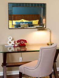 modern glass desk in a bedroom with wooden legs and an upholstered chair