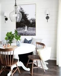 dining furniture ideas white pedestal table wood chairs sconces b w art