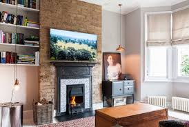 bright living room floating shelves exposed brick fireplace column