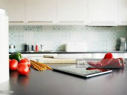 kitchen counter with food. Digital Tablet, Red Peppers And Tomatoes On Kitchen Counter With Food