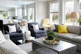 gray sofa with bright yellow pillows and black waterfall coffee table