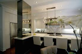 contemporary kitchen features polished nickel and lucite rectangular chandelier over black island topped with contrasting white countertops framing dual