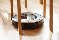 Robotic Vacuum Cleaner On Laminate Wood Floor Smart Cleaning Tec Royalty  Free Stock Images