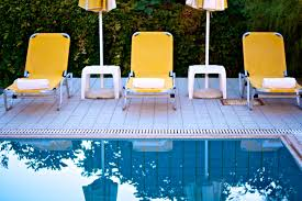 triple floating pool lounge chair on wooden deck with yellow accent