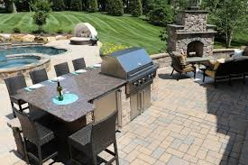 techo bloc outdoor kitchen with lower bar seating area fridge and gas grill