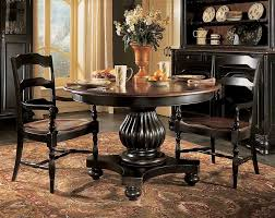 old antique 36 inch solid wood round pedestal dining table painted with black color and 2 ladder chairs on brown carpet tiles beside oak display furniture