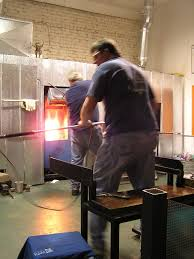 glass blowersglass blowers work in tandem to make a blown glass vase in the hot glass studio at the conway glass center