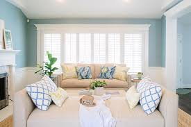 beige and blue living room features blue paint on upper walls and wainscoting on lower walls lined with a beige nailhead sofa adorned with blue ikat pillows