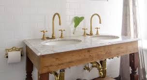 a bathroom countertop with two sinks two brass faucets marble countertops and white