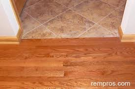 solid hardwood floor in transition with porcelain tile to trim