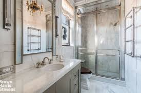 another look at the bathroom showcasing its smooth sink and shower area lighted by a chandelier