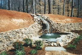 large scale tennessee fieldstone retaining wall w steep flowing stream waterfall into pond w