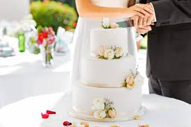 bride and groom cutting cake wedding cake tiers sizes and servings everything you