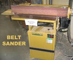 large belt sander. a belt sander has large sandpaper that sands as stock is pressed against it. sanders are called \