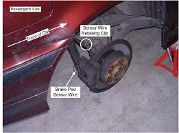 bmw e36 replacing brake pads and rotors step 5 starting on the passenger side remove the brake pad wear sensor cable from the retaining clip