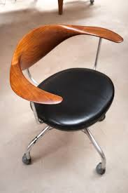 Swivel office chair with medium brown curved solid wood paired with a black  leather seat cushion and metal legs and arms.