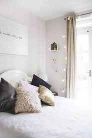 What a pretty pastel room. The framed plant the festoon lights hanging from  the curtain rail give it such a cosy feel!