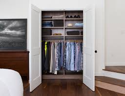 The combination of a dark wood finish with white allows this closet to  seamlessly fit within