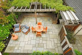 Stone patio with orange chairs and table.
